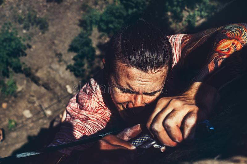 Young Climber Man On The Rock Wall, Close-up Of Male Hands With Tape In Magnesium Powder. A young man climbs up a cliff, close-up, arms a powder of magnesia royalty free stock photography