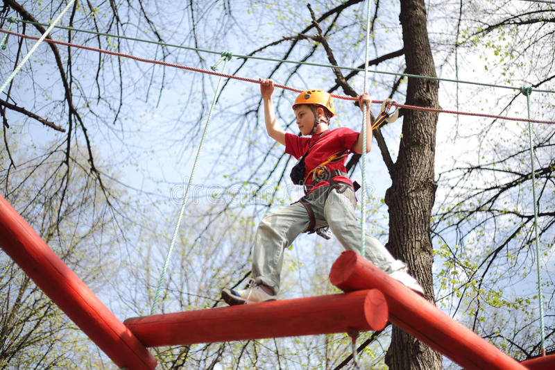 Young climber skilfully go on a suspension bridge. In high ropes course royalty free stock image