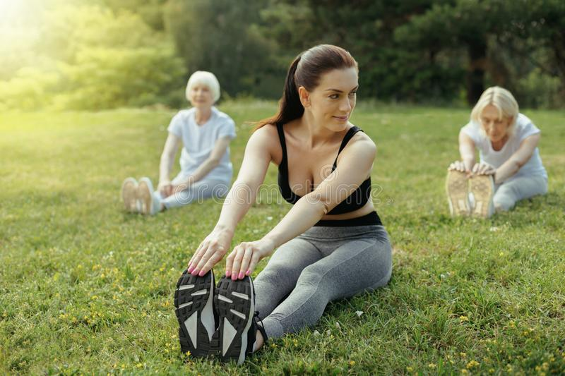 Young coach showing elderly people stretching exercise royalty free stock image