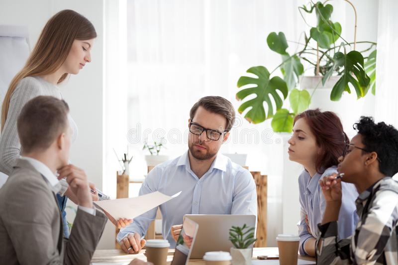 Young coach woman presenting report to colleagues in office. Diverse millennial businesspeople company sitting at seminar presentation in office boardroom. Coach stock images