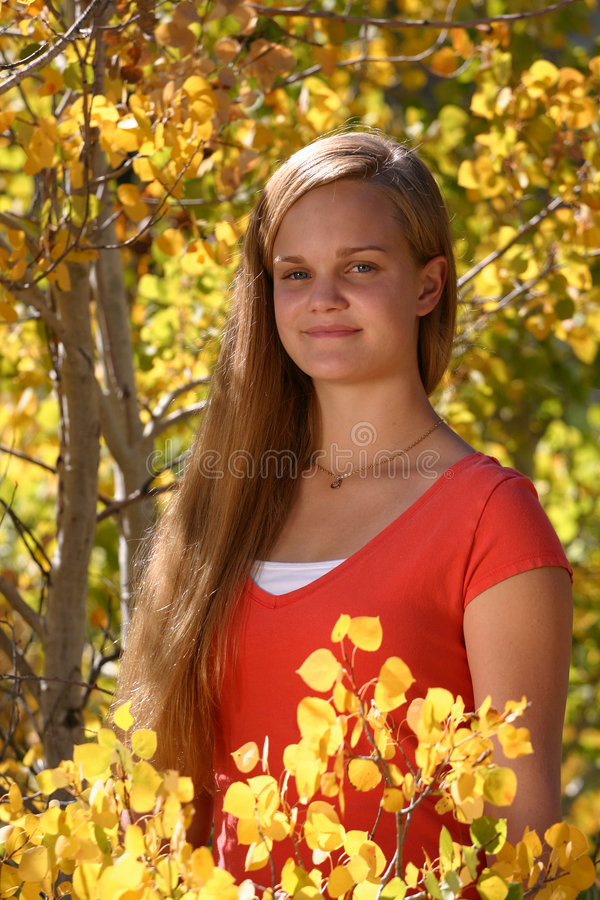 Young Coed in the Fall. A young teenage coed in a bright yellow fall setting, thinking about going back to school royalty free stock images