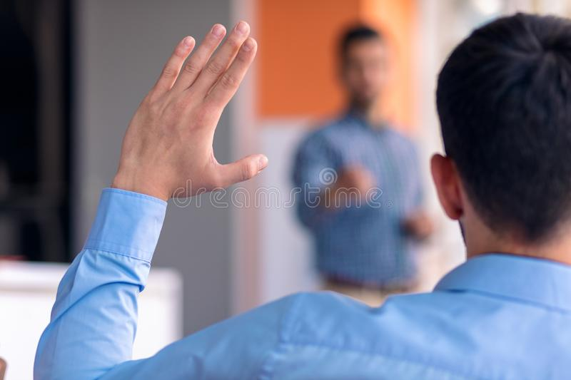 Young colleagues raising hands at the business meeting in office.  stock image