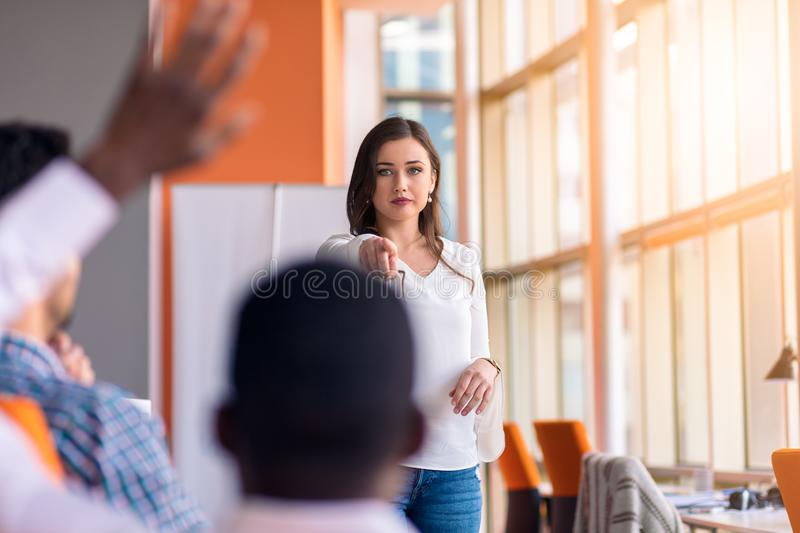 Young colleagues raising hands at the business meeting in office.  stock photo