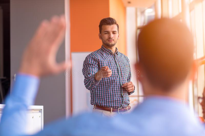 Young colleagues raising hands at the business meeting in office.  stock photography
