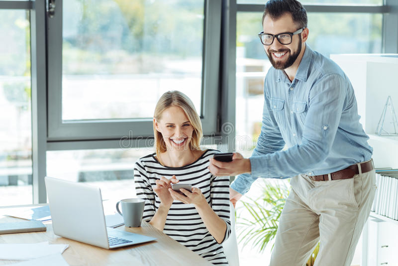 Young colleagues showing each other funny posts and laughing. Genuine amusement. Pleasant young men showing his cheerful female colleague funny posts on social stock photography
