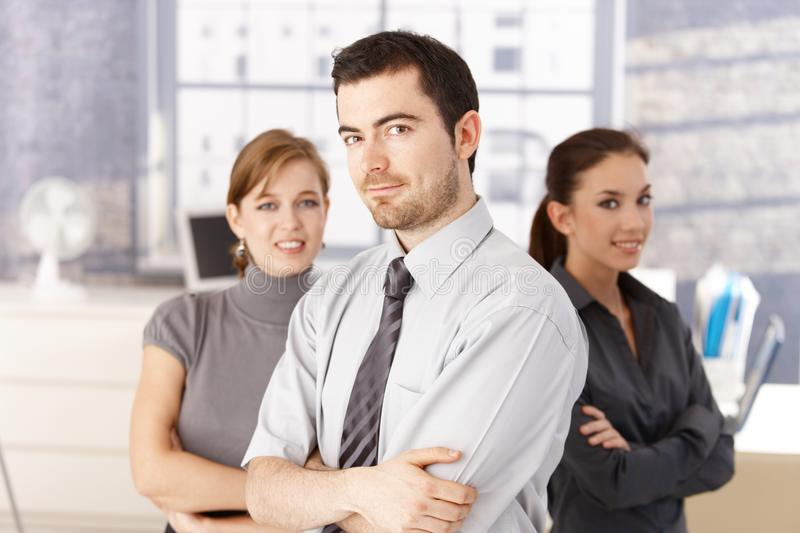 Young colleagues standing in office arms crossed royalty free stock photography