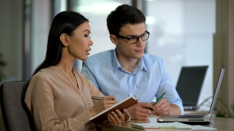 Young colleagues watching online training laptop making notes, planning strategy. Stock photo stock photo