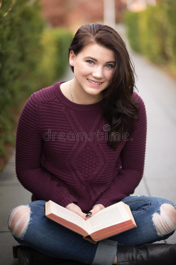 Young college age woman reading book outdoors. royalty free stock image
