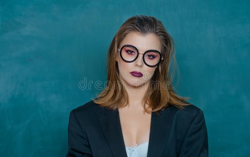 Young college student at hard exam preparation in study hall looking sensuality. Young sensual student near chalkboard royalty free stock photos