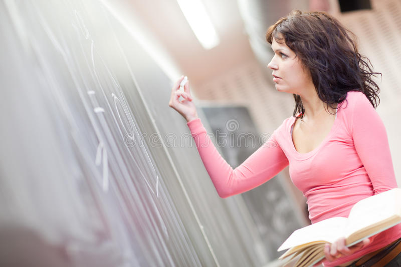 Young college student writing on the chalkboard. Pretty young college student writing on the chalkboard/blackboard during math class (shallow DOF; color toned royalty free stock image