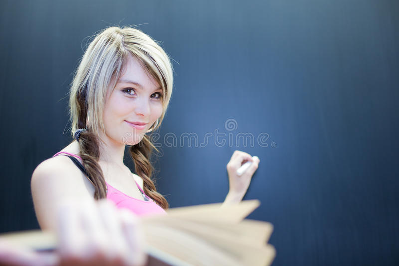 Young college student writing on the chalkboard. Pretty young college student writing on the chalkboard/blackboard during math class (shallow DOF; color toned royalty free stock images