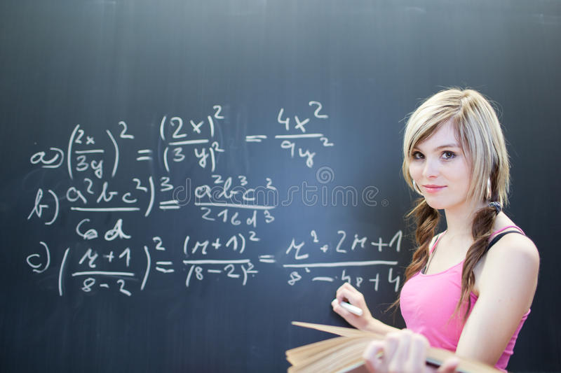 Young college student writing on the chalkboard. Pretty young college student writing on the chalkboard/blackboard during math class (shallow DOF; color toned stock images
