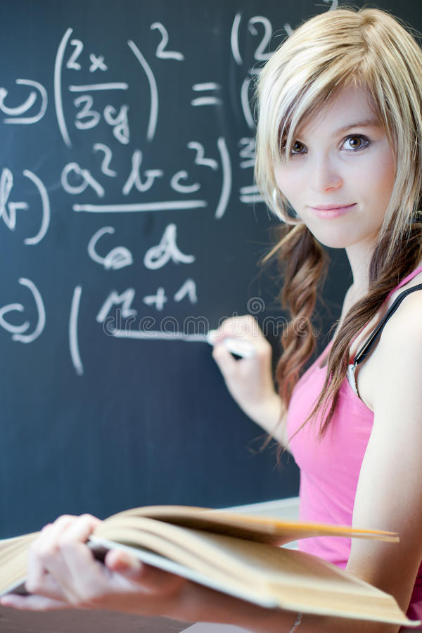 Young college student writing on the chalkboard. Pretty young college student writing on the chalkboard/blackboard during math class (shallow DOF; color toned royalty free stock photos