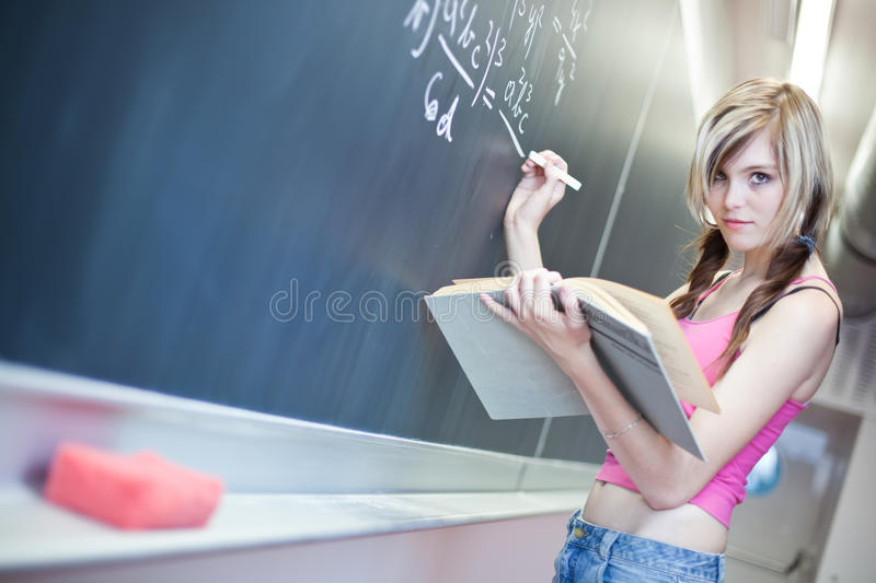 Young college student writing on the chalkboard. Pretty young college student writing on the chalkboard/blackboard during math class (shallow DOF; color toned royalty free stock photo