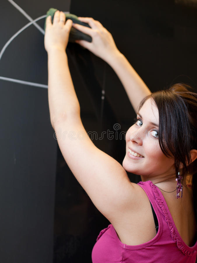 Young college student writing on the chalkboard. Pretty young college student writing on the chalkboard/blackboard during math class (shallow DOF; color toned stock photography