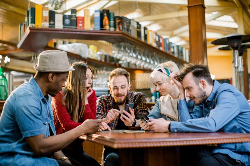 Young college students or coworkers using smartphones together at coffee shop, diverse group. Casual business, freelance royalty free stock images
