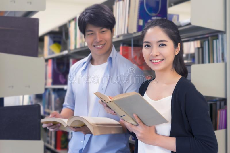 Young college students reading a book together in library. Education and school concept. royalty free stock images