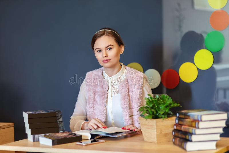 Young college woman sitting at table in campus cafe reading new book series royalty free stock images