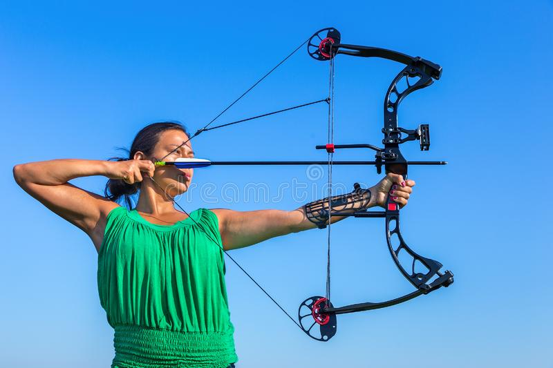 Young colombian woman aims arrow of compound bow. Young black haired colombian woman aiming arrow of compound bow in blue sky royalty free stock image