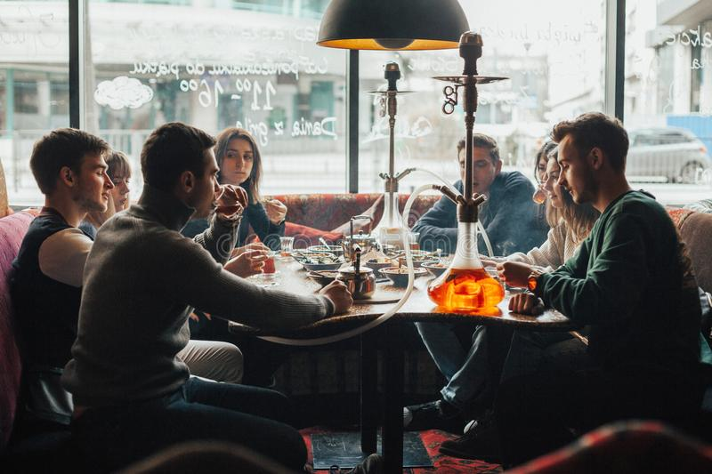 Young company is having fun and eating in bar. smoking a hookah, communicating in an oriental restaurant. stock images