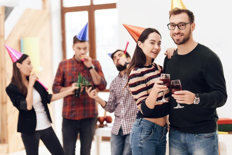 Young company workers are talking near a white board. They celebrate a corporate holiday and are dressed in holiday caps and have fun royalty free stock photo