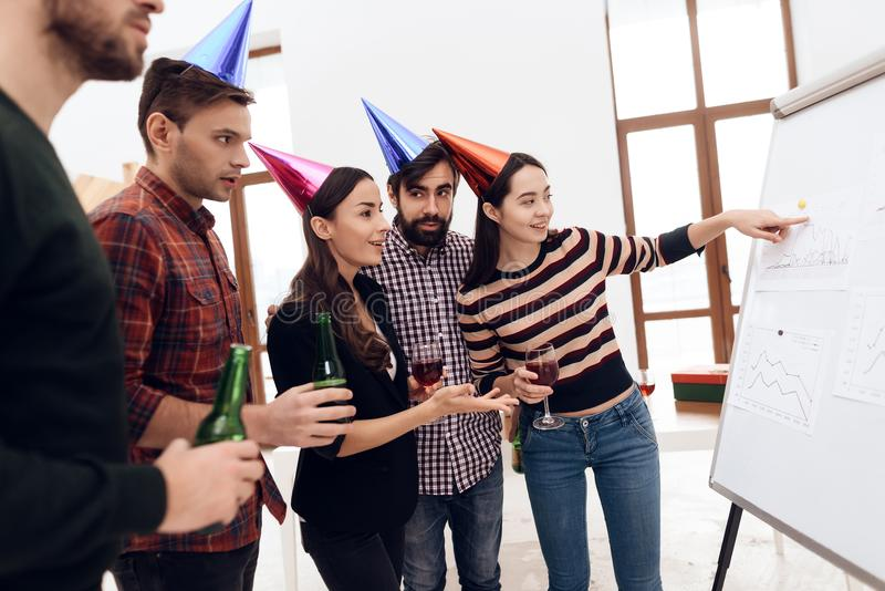 Young company workers are talking near a white board. They celebrate a corporate holiday and are dressed in holiday caps and have fun royalty free stock images