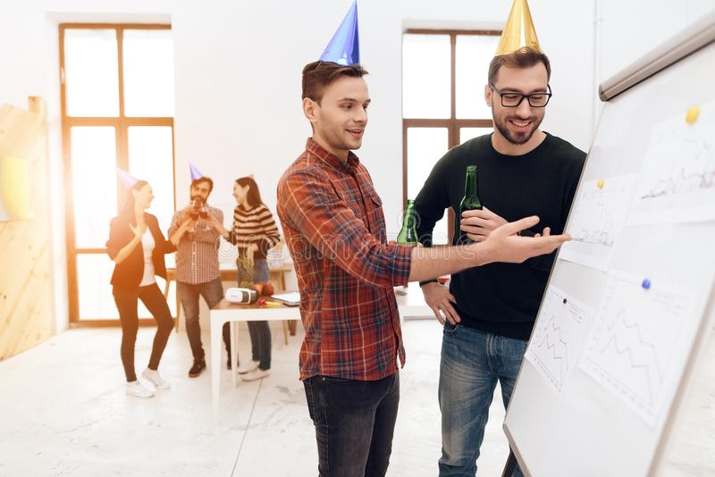 Young company workers are talking near a white board. They celebrate a corporate holiday and are dressed in holiday caps and have fun stock image