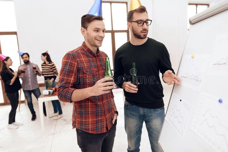 Young company workers are talking near a white board. They celebrate a corporate holiday and are dressed in holiday caps and have fun stock photography