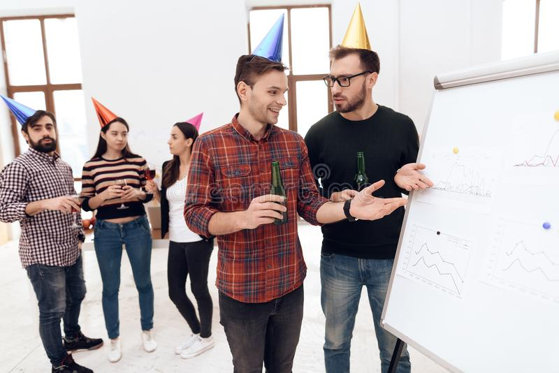 Young company workers are talking near a white board. They celebrate a corporate holiday and are dressed in holiday caps and have fun stock photo