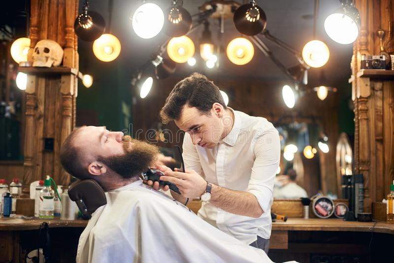 Male client with beard sitting in hairdresser chair. Serious man with long brown beard. Modern popular lumberjack style. Young concentrated barber shaving and stock photos