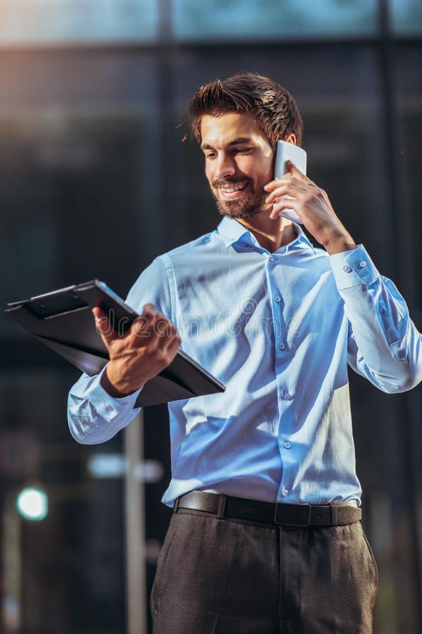 Young concentrated businessman walking outdoors on the street using mobile phone. Photo of a young concentrated businessman walking outdoors on the street using stock photos