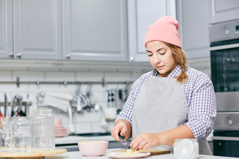 Stylish cook cutting fruit stock image