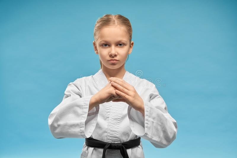 Karate girl with black belt practicing hands position. Young concentrated karate girl practicing hands position. Pretty junior in white kimono with black belt stock photo