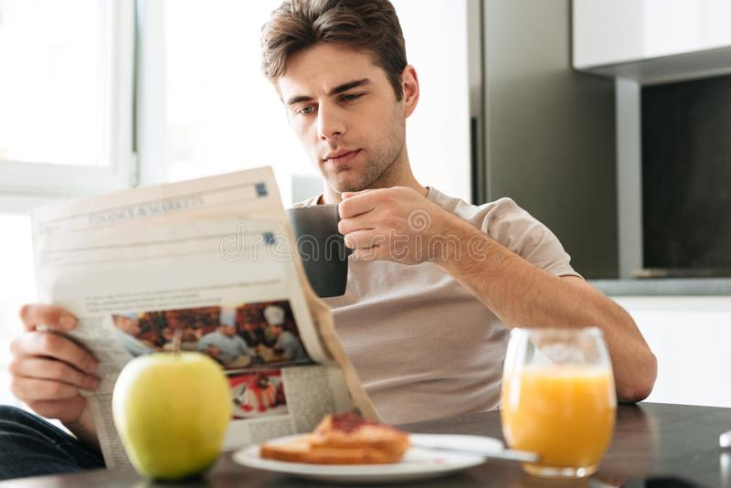Young concentrated man reading newspaper while sitting in kitchen royalty free stock photography