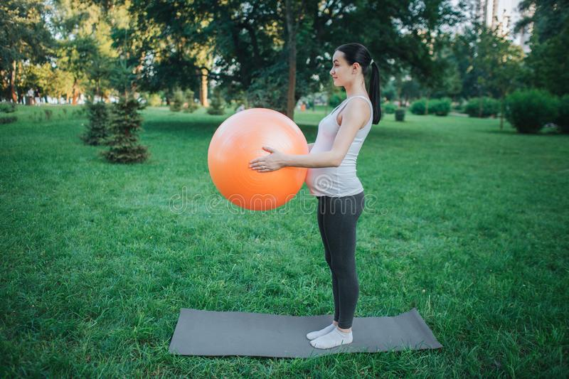 Young concentrated pregnant woman stand on yoga mate in park and hold orange fitness ball. She exercising. stock photo