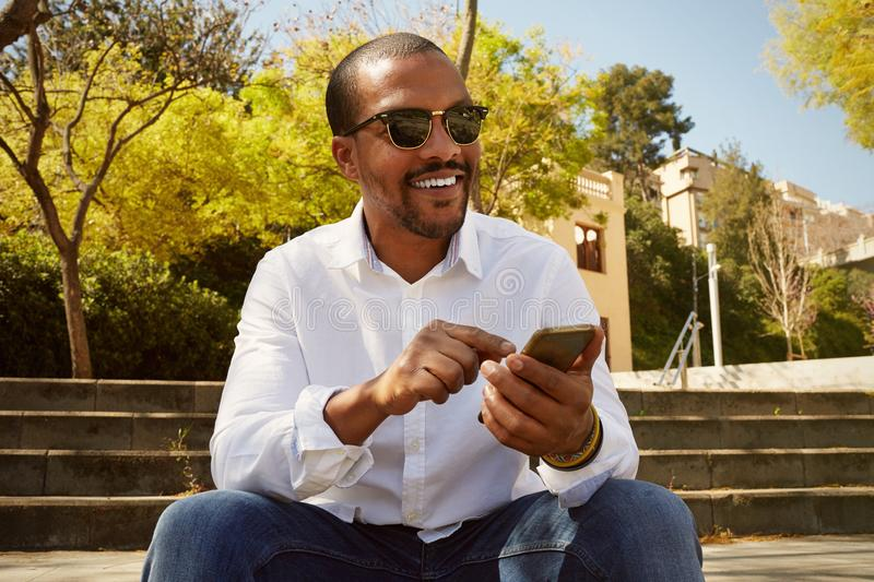 Young confident african man pointing hand on smartphone while sitting at sunny city park.Concept of happy business stock image