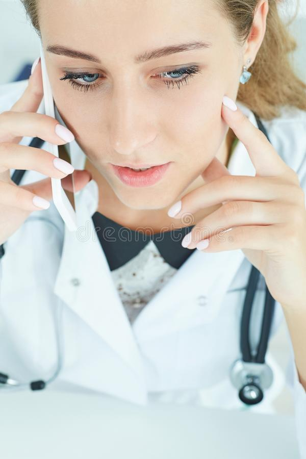 Young confident attractive female doctor talking on phone with patient. Top view. Remote health care concept. stock images