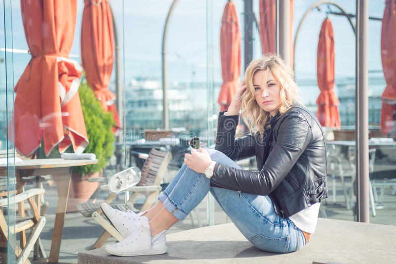 Young confident attractive woman sitting ouside near city cafe royalty free stock image