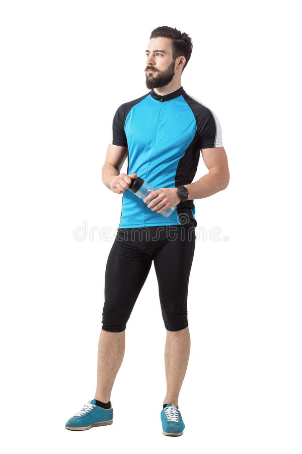 Young confident bearded cyclist holding water bottle relaxing. Full body length portrait isolated over white studio background royalty free stock image