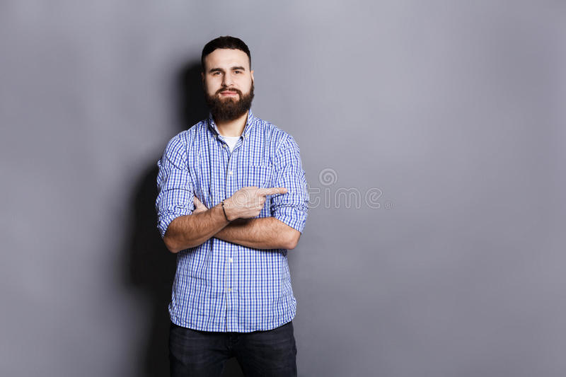 Young confident bearded man point away stock image