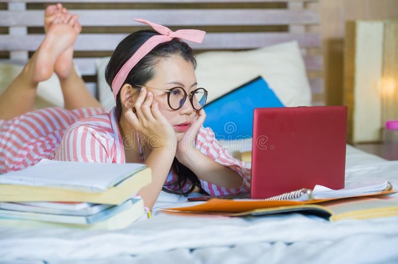 Young confident and beautiful Asian Korean student woman preparing University exam studying at home bedroom with laptop computer royalty free stock photos