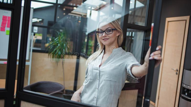 Young confident business woman in glasses on the background of the workspace. stock image