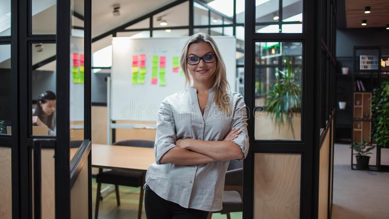 Young confident business woman in glasses on the background of the workspace. royalty free stock images