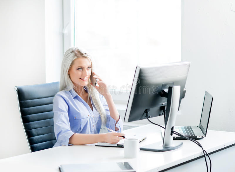 Young and confident business woman working in office. Young, attractive and confident business woman working in office stock images