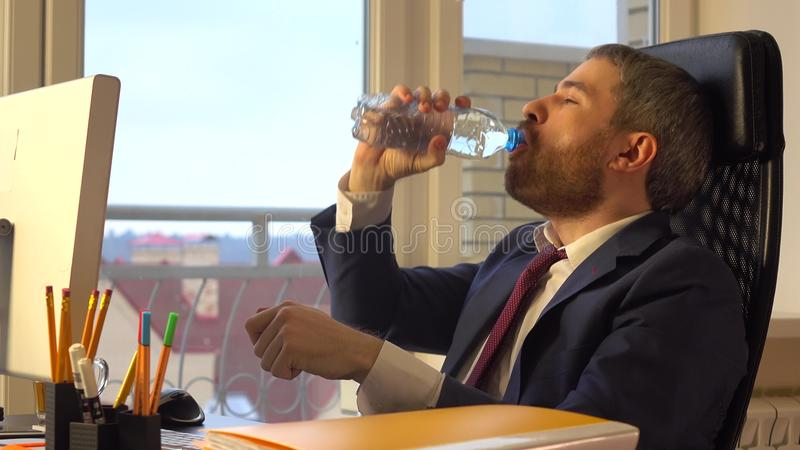 Young confident businessman drinking water at his desk royalty free stock images