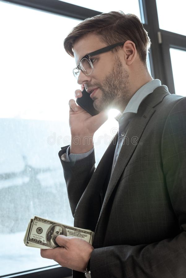 Young confident businessman holding money and talking on the smartphone royalty free stock images