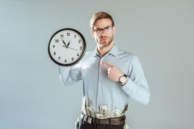 Young confident businessman pointing on clock royalty free stock photos
