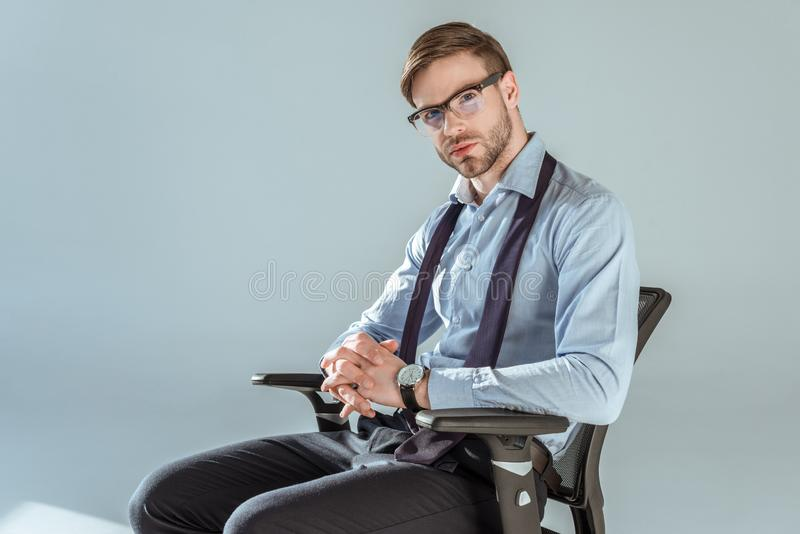 Young confident businessman sitting on chair with hands clenched royalty free stock photography