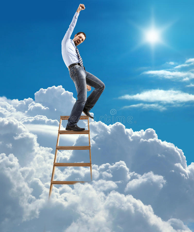 Young confident businessman standing at the ladder high in the sky reaches the top stock images