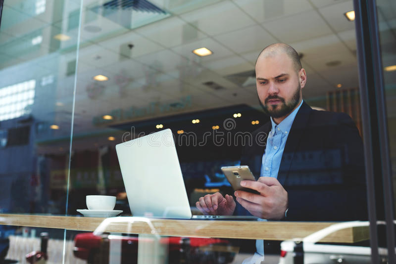 Young confident businessman use cell phone during coffee work break. Serious man entrepreneur is reading text message from the bank about his account after he royalty free stock photography